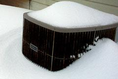 central air conditioning compressor partially covered with snow