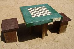 chess game table and benches on a sandy beach